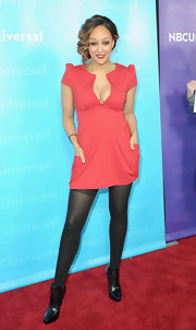 Tia Mowry wore a pink deep-plunging cocktail dress with tights to the All-Star Party.