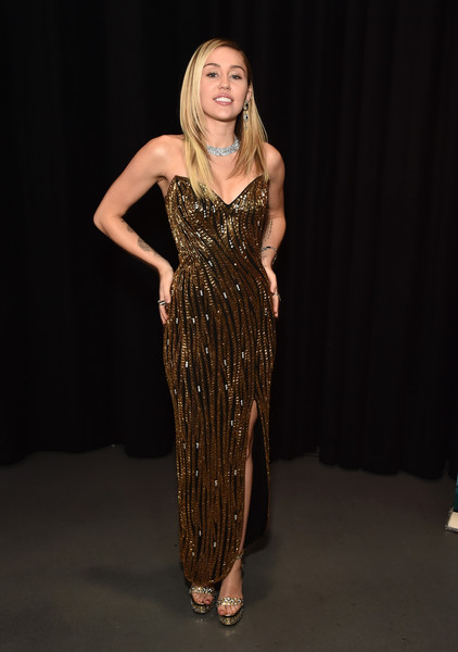 Miley Cyrus kept the sparkle going with a pair of embellished gold platforms.