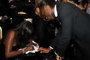 Didier showed off a brown beaded bracelet while waiting for an autograph from Naomi Campbell.