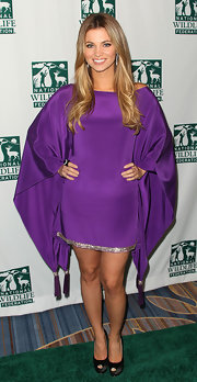 Amber Lancaster was draped in a deep purple dress with exaggerated sleeves and tassel detailing at the hemline.