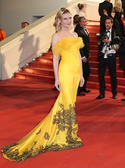 Kirsten Dunst looked supremely glamorous at the Cannes screening of 'The Neon Demon' in a yellow spaghetti-strap fishtail gown by Maison Margiela, featuring black lace accents and a ruffled neckline.