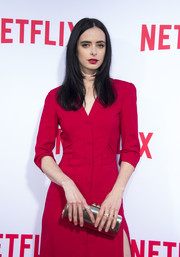 Krysten Ritter's gold tube clutch worked beautifully with her red dress at the 'Jessica Jones' FYC screening.