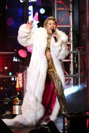 Miley Cyrus went ultra-luxe in a floor-sweeping white fur coat by The Blonds layered over a gold sequin crop-top and pants at the New Year's Eve celebration in Times Square.