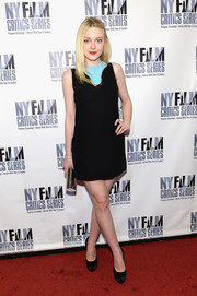 Dakota Fanning styled her outfit with a silver tube clutch.