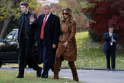 Melania Trump matched her coat with brown over-the-knee boots by Saint Laurent.