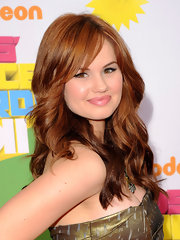 Debby Ryan simply glowed on the orange carpet with radiant red tresses. She parted her tresses down the side and opted for loose flowing curls.