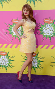 Debby Ryan chose a pale yellow brocade dress with a fun and flirty cutout for her look at the Kids' Choice Awards.