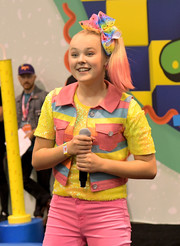 JoJo Siwa layered a multicolored striped vest over a yellow sequined top for her 2018 VidCon look.