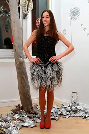 Olivia looked like a subdued Vegas showgirl in this beaded feather ensemble. She paired the black and gray dress with red pumps. Her hair was in an effortless style.
