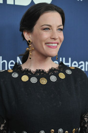Liv Tyler dressed up her casual ponytail with a pair of gold crucifix earrings by Dolce & Gabbana.
