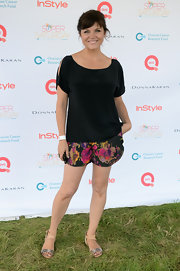 Tiffani Thiessen's cold-shoulder black blouse let her bold floral shorts do all the talking!