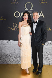 Amal Clooney looked ultra elegant in a fringed champagne one-shoulder dress by Armani Prive at the Omega 50th Anniversary Moon Landing event.