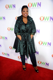 Oprah loves to wear iridescent styles. She donned a green evening coat with a tie belt and pockets over a pair of jeans.