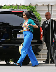 Michelle Obama teamed a green cardigan with a print blouse and blue slacks for a vibrant finish during a Sidwell Friends School event.