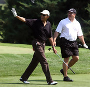 Obama sports white and brown golf shoes with gold accents for his walk down the fairway.