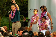 (AFP OUT) President Barack Obama and his family Malia Obama, Michelle Obama and Sasha Obama host a luau for members of Congress and their families on the South Lawn of the White House June 25, 2009 in Washington, DC. In a celebration of the president's home state, the South Lawn was decorated with tiki torches and palm huts and the meal prepared by famous Hawaiian chef Alan Wong.