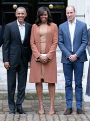 Michelle Obama was monochromatic-chic in a blush wool coat layered over a nude top and lace skirt while attending a dinner at Kensington Palace.