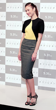 Olga Kurylenko chose a black-and-yellow triangular paneled top and a fitted tweed skirt for her look at the photocall for 'Oblivion' in Tokoyo.