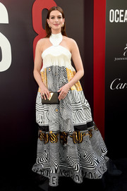 Anne Hathaway coordinated her dress with a black and gold box clutch by Jill Milan.