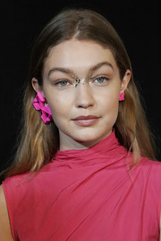 A pair of mismatched hot-pink earrings finished off Gigi Hadid's runway look.