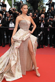 Natasha Poly looked fiercely glam in a structured gold one-shoulder gown by Atelier Versace at the 2019 Cannes Film Festival screening of 'Oh Mercy!'