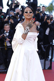 Rihanna's long red nails added a pop of color to her white coat and gown ensemble.