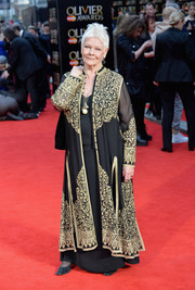 Judi Dench arrived for the Olivier Awards looking exotic in a gold-embroidered black robe.