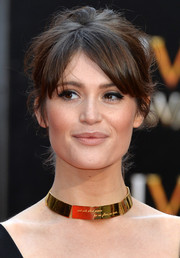 Gemma Arterton went for retro cuteness with this messy updo and parted bangs at the Olivier Awards.