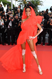 Winnie Harlow styled her dress with gold slim-strap heels by Jimmy Choo.