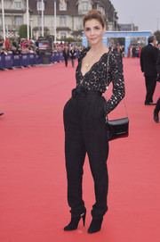 Clotilde Courau paired her jumpsuit with a black patent shoulder bag.