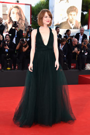 Emma Stone walked the Venice Film Festival red carpet looking dreamy in a dark green Valentino Couture gown, featuring a deep-V neckline and a voluminous tulle skirt.