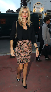 Adding some color to her all black look, Sienna paired her cropped jacket with a Thompson leopard print skirt.