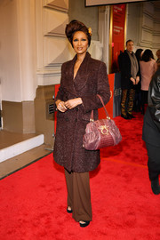 Iman accessorized with a mauve leather tote.