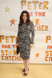 Debra Messing paired rich brown peep toe pumps with her bold animal print dress for the opening night of 'Peter and the Starcatcher.'
