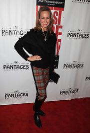 Melora donned casual flat boots with unexpected plaid pants. The actress tames the loud look with a slouchy black sweater.