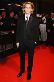 Jamie Campbell Bower looked so fashionable in a black suit accentuated with a fringe scarf.