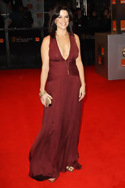 Neve Campbell positively beamed on the red carpet of the Orange British Academy Film Awards in a floor-length maroon dress.