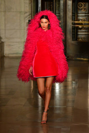Bella Hadid got majorly glam in a red feather cape for the Oscar de la Renta runway show.