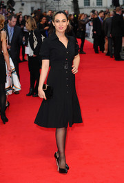 Asli Bayram accessorized with a velvet clutch for an elegant all-black look.