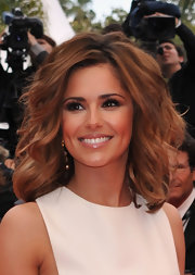 Cheryl wears a beautiful pink lipstick with a layer of gloss.