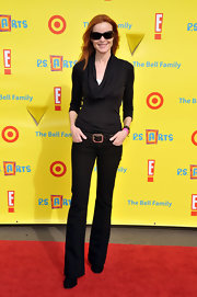 Marcia Cross ups the coolness factor of her cowl neck sweater and bell bottom jeans in a pair of dark shades.