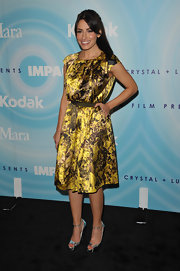 Sarah Shahi paired her feminine gold satin dress with metallic silver ankle-strap peep-toes.