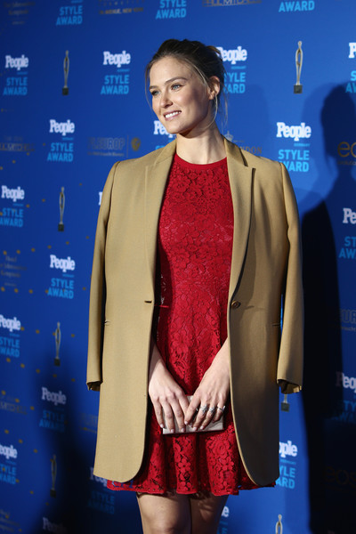 Bar Refaeli posed on the People Style Awards red carpet wearing a tan wool coat over a red lace dress.