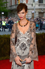 Karlie Kloss attended the Met Gala carrying a stylish gray crocodile clutch.