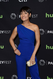 Grace Gealey paired a cream and gold hard-case clutch with a royal-blue jumpsuit for her PaleyFest Los Angeles look.