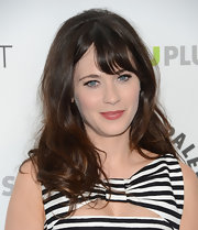 Zooey Deschanel stuck to her signature '60s-inspired look with a slightly teased wavy 'do with blunt bangs.