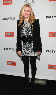 Anna wears a patent leather belt over her leopard print dress and under her black blazer.