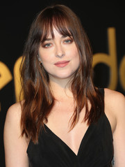 Dakota Johnson styled her hair with gentle waves and wispy bangs for the Panthere De Cartier party.