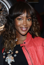 Naomi Campbell's pretty waves and brow-length bangs are casually chic. To try her look at home, curl one-inch sections with a medium-barreled curling iron and add a very slight bend to the end of bangs. To finish the look tousle curls with fingertips.
