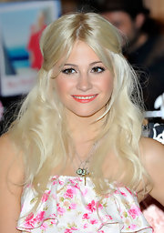 Pixie Lott styled her platinum blond tresses in soft fluffy curls that were elegantly parted down the center.